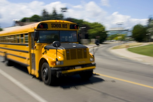 Yellow school bus speeding on the road in motion.
